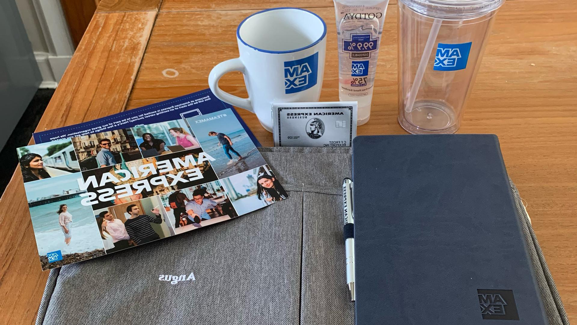 a goody bag from American express including a cup, mug, notebook and a bag